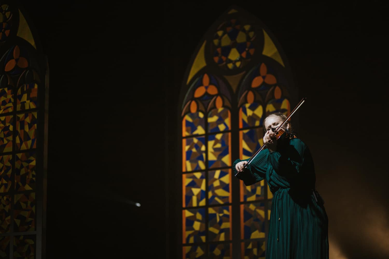 Huslistka hrá na husle na pódiu, v pozadí kulisa vitráže